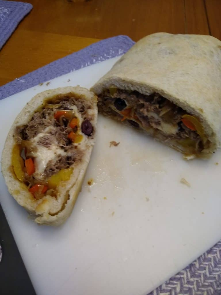 sliced cheese steak stromboli with sauteed peppers, onions, and garlic